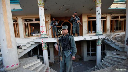 Afghan policemen stand guard at an election commission office after an attack by suicide bombers and gunmen in Kabul.