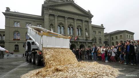 """A truck dumps five-Rappen coins in the center of the Federal Square during a an event organized by the Committee for the initiative """"CHF 2,500 monthly for everyone"""" (Grundeinkommen) in Bern, Switzerland. The Committee delivered 126,000 signatures to th..."""