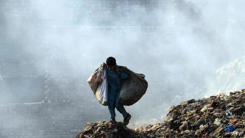 A Pakistani child looks for items to be recycled amid garbage on the outskirts of Lahore.