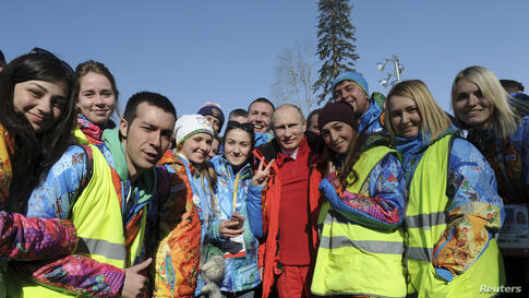 Russian President Vladimir Putin poses for a photograph with volunteers during his visit to watch the men's cross country skiing relay during the Sochi 2014 Olympic Winter Games at Laura Cross-Country Ski and Biathlon Center near Krasnaya Polyana, Russ...