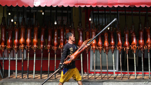 """A worker carries a roasted pig outside a store in Quezon city, north of Manila, Philippines. Roasted pig is traditionally served during a Christmas eve dinner called """"Noche Buena"""" in the predominantly Roman Catholic nation."""