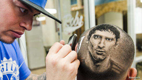 """Hair artist and master barber Rob Ferrel (L), known as """"Rob the Original"""", cuts the likeness of Argentine soccer player Lionel Messi on the head of customer Vincent Hernandez, at his barbershop in San Antonio, Texas, USA, June 30, 2014."""
