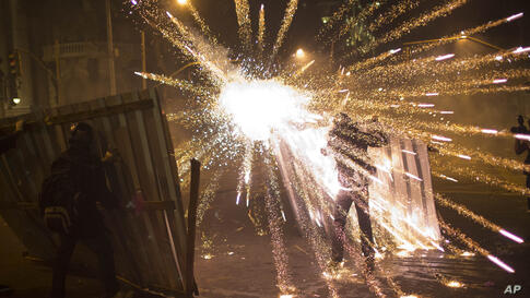 A burst of fireworks go off near members of the so-called Black Bloc anarchist group during clashes with police after a march of striking teachers took place to mark National Teachers Day, in Rio de Janeiro, Brazil, Oct. 15, 2013.