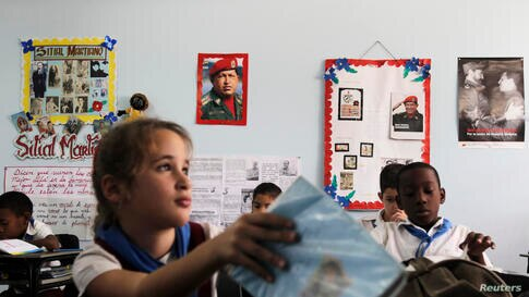 Schoolchildren attend a class while sitting near photographs of Venezuela's late President Hugo Chavez and Cuba's former President Fidel Castro at the Hugo Chavez Frias primary school in Havana. Different activities will be held in Cuba and in other co...
