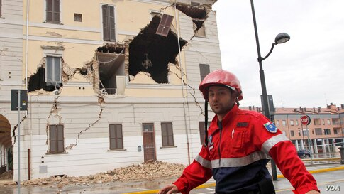 A civil protection volunteer walks past the damaged town hall building in St. Agostino, Italy,May 20, 2012. One of the strongest earthquakes to shake northern Italy rattled the region around Bologna, a magnitude-6.0 temblor that killed at least four peopl