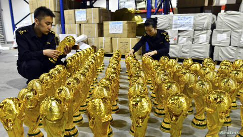 Customs officers look at confiscated counterfeit FIFA World Cup replica trophies in Yiwu, Zhejiang province, China, April 16, 2014. The local customs office seized a total of 1,020 unauthorized FIFA World Cup replica trophies before they were shipped o...