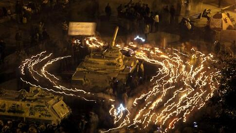 Anti-government protestors hold candles as they walk surrounding an Egyptian Army tank at Tahrir square in Cairo, Egypt, Wednesday, Feb. 9, 2011. Protesters appear to have settled in for a long standoff, turning Tahrir Square into a makeshift village with