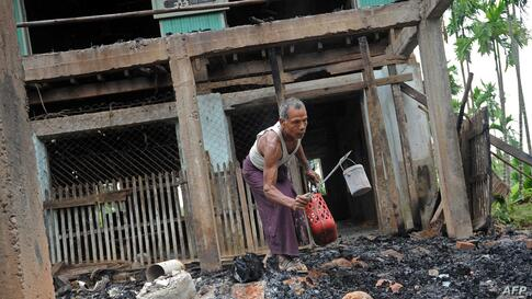 A man salvages items from the burnt area of a mosque following communal clashes in Thabyu Chi village near Thandwe, in Burma's western Rakhine state.