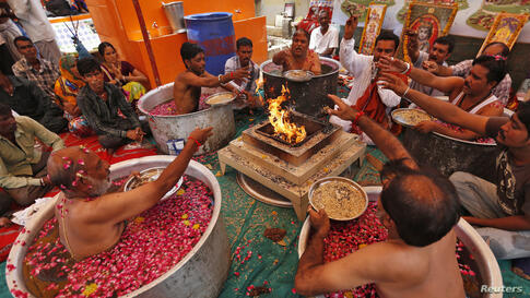 """Hindu priests sit in cauldrons of water and rose petals as they perform the """"Parjanya Varun Yagam"""", a special prayer for rain, in the western Indian city of Ahmedabad."""