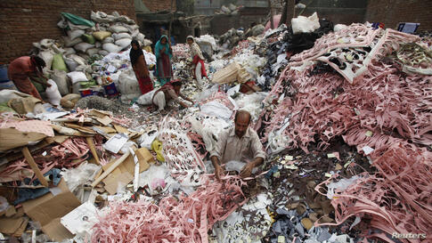 A man separates cardboard and Rexine for recycling, to be used for the insides of leather shoes, at a compound in Lahore, Pakistan.