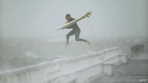 A surfer jumps off the pier into Port Phillip Bay to take advantage of the waves as a storm lashes the Melbourne area, Japan.