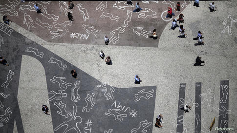 People walk over drawings depicting chalk outlines of bodies during a protest at Carioca square in downtown Rio de Janeiro, Brazil. The drawings represent the 4,000 victims of violence who died in Rio de Janeiro state in 2012, according to the group JM...