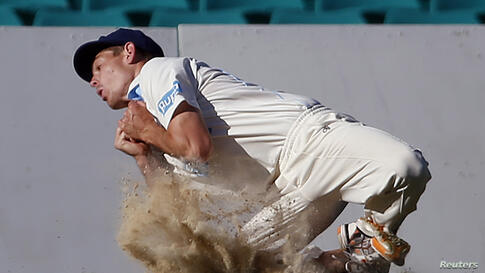 Cricket Australia Invitational XI player Daniel Hughes kicks up dirt as he takes a catch to dismiss England's Kevin Pietersen for 57 runs during their warm-up match at the Sydney Cricket Ground, Australia.