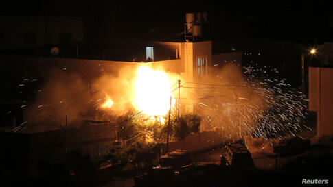 Flames are seen after a blast on the top floor of the family home of an alleged abductor in the West Bank City of Hebron. The bodies of three missing Israeli teenagers were found in the occupied West Bank and Israel vowed to punish Hamas, the Palestini...