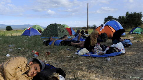 Migrants rest on a field at the border between Greece and Macedonia, Aug. 21, 2015.