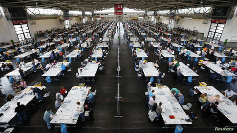 About 1,400 electoral officials sort ballot papers after the conclusion of voting in the European Parliament elections at the Messe in Munich, Germany.