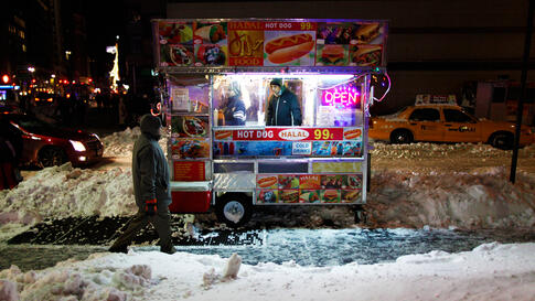 Dec. 28: A man walks past a food cart in New York City. The blizzard dumped 29 inches of snow on some areas and severely disrupted air and rail travel. (Gary Hershorn/Reuters)