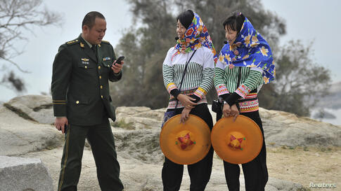 A People's Liberation Army officer looks at his mobile phone as he speaks with two Hui'an tourist guides in Hui'an county, Fujian province, China, Dec. 8, 2013.