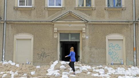 A woman stands on a wall of sandbags in front of a house in Dresden, eastern Germany. Heavy rainfalls have caused flooding along rivers and lakes in Germany, Austria, Switzerland and the Czech Republic.