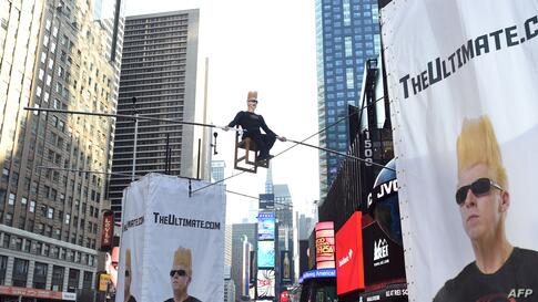 International circus superstar Bello Nock takes over Times Square in New York City as he spends eight hours on a high wire above New Yorkers in the first of several big stunts he is doing this summer.