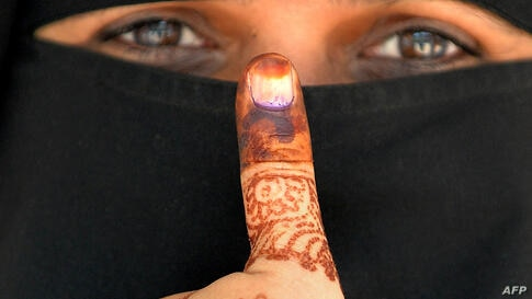 An Indian Muslim woman displays her inked thumb after casting her vote at a polling station in Bangalore.