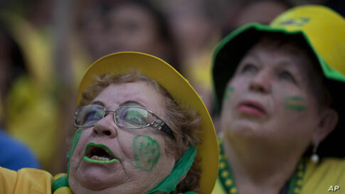 A fan of the Brazilian national soccer team watches the Mexico vs. Brazil match at the FIFA Fan Fest, during the 2014 soccer World Cup in Sao Paulo, Brazil, June 17, 2014.