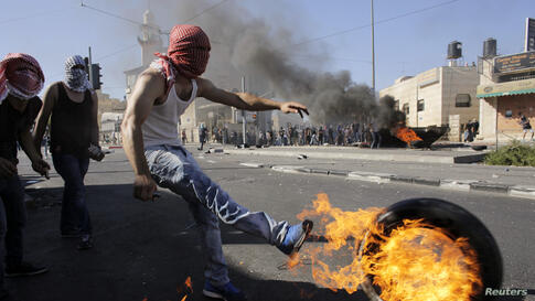 A Palestinian kicks a tire after setting it ablaze during clashes with Israeli police in Shuafat, an Arab suburb of Jerusalem. The discovery of a body in a Jerusalem forest raised suspicions that a missing Palestinian youth had been killed by Israelis ...