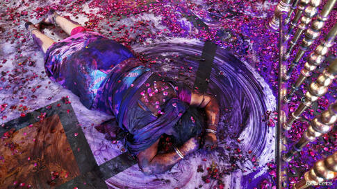 A Hindu woman prays while lying on the floor of a temple during Holi celebrations in the western Indian city of Ahmedabad. Holi, also known as the Festival of Colours, heralds the beginning of spring and is celebrated all over India.