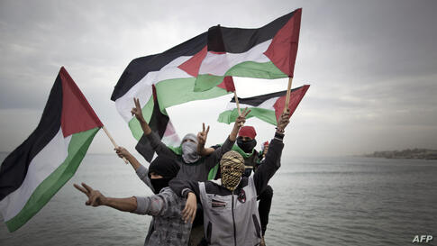 """Palestinians wave national flags before a convoy of boats is launched at the initiative of the """"Intifada Youth Coalition"""" (IYC) to break the naval blockade of Gaza as a protest against the Israeli siege of the port in Gaza city."""