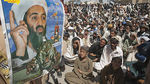 Supporters of Pakistani religious party Jamiat-e-ulema-e-Islam are seen near an image of al-Qaeda leader Osama bin Laden during an anti-U.S. rally on the outskirts of Quetta May 6, 2011. About 1,500 Pakistani Islamists protested on Friday against the kill