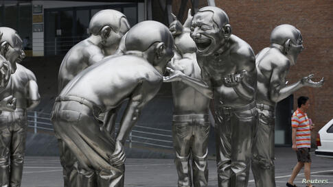 A man walks past a group of art works by Chinese artist Yue Minjun on display outside the Today Art Museum in Beijing.