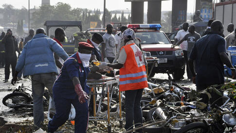 Rescue workers work to recover victims at the site of a blast at the Nyanya Motor Park, about 16 kilometers (10 miles) from the center of Abuja, Nigeria.