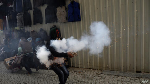 A Kurdish student protester launches fireworks against Turkish riot policemen in downtown Istanbul during an anti-government protest marking the second anniversary of a Turkish military air strike aimed at Kurdish rebels that killed 34.