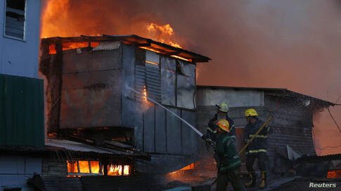 Firemen try to extinguish a fire as houses burn in a squatter colony in Quezon City, Metro Manila.
