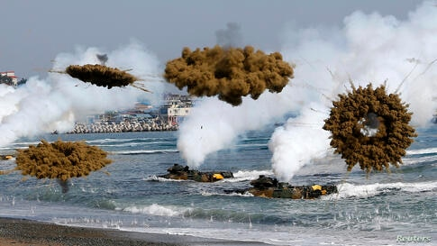 Amphibious assault vehicles of the South Korean Marine Corps fire smoke bombs as they move to land on shore during a U.S.-South Korea joint landing operation drill in Pohang.
