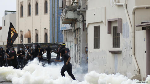 An anti-government protester throws a stone at riot police amid teargas fired by the police during clashes in the village of Diraz, west of Manama, Bahrain. Protests following the death of 20-year-old Fadhel Abbas threatened to sour a new attempt to re...