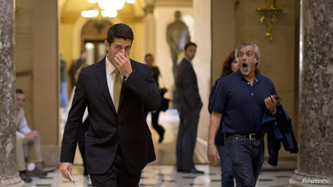 A tourist (R) reacts as U.S. Representative Paul Ryan walks in Hall on Capitol Hill in Washington, D.C., Oct. 11, 2013.