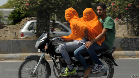 Indian motorcyclists cover their heads as they travel in the heat in Amritsar. Amritsar and Ludhiana in Punjab and Hisar and Bhiwani in Haryana have been reeling under severe heat conditions with temperatures hovering between 45-47°C (113-116°F).
