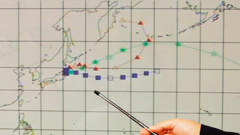 An officer at the Hong Kong Observatory shows a forecast trajectory of radiation releases from Japan during a news conference in Hong Kong Wednesday. Indicators in red triangles, blue squares and green stars project wind directions of different altitudes.