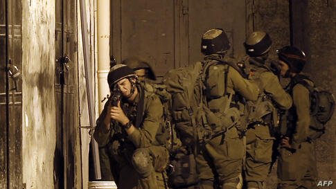 Israeli soldiers take part in a search operation in the West Bank village of Awarta as part of the operation to locate the three teenagers the army believes were abducted by Islamist movement Hamas on June 12.