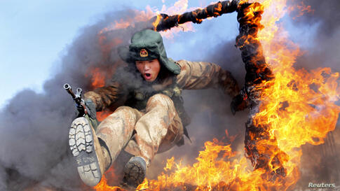 A frontier soldier from the People's Liberation Army jumps through a ring of fire as part of training in Heihe, Heilongjiang province, China.
