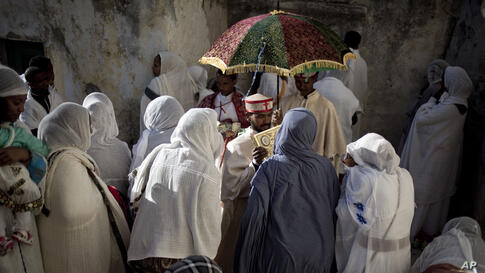 An Ethiopian Orthodox Christian priest holds a holy book for women to kiss at Deir El Sultan in the Church of the Holy Sepulcher, traditionally believed by many to be the site of the crucifixion and burial of Jesus Christ, during Palm Sunday services i...