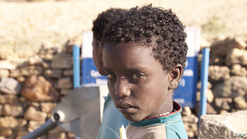 A girl holding sugarcane at a well in Endaselassie. Ethiopia, February 2012. (Photo: Water.org)