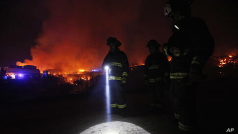 A firefighter shines a flashlight as he stands with others near burning homes as a forest fire rages towards urban areas in the city of Valparaiso, Chile.