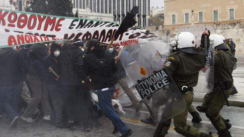 Riot police in Athens clash with protestors opposing severe cuts in government spending earlier in December