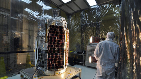 In a clean room at Vandenberg Air Force Base's processing facility in California, a technician conducts a solar array illumination test on NASA's NuSTAR spacecraft, February 2, 2012. (NASA)