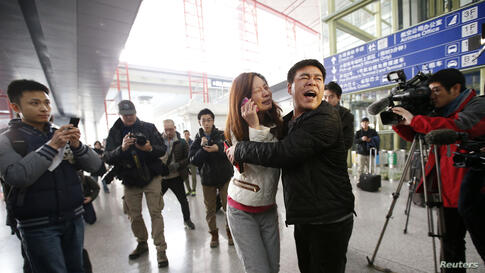 A relative of a passenger onboard Malaysia Airlines flight MH370 cries as she talks on her mobile phone at the Beijing Capital International Airport in Beijing, China. The Malaysia Airlines flight carrying 227 passengers and 12 crew lost contact with a...