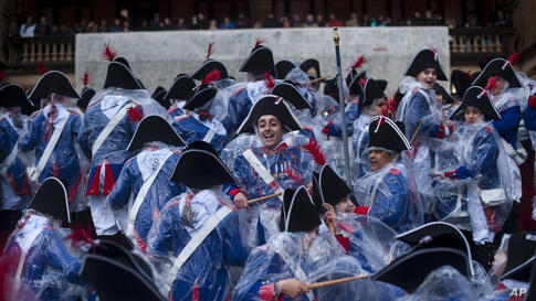 Tamborilleros wearing their uniforms try to shelter from the rain, as they march in the traditional ' La Tamborrada', during 'El Dia Grande', the main day of San Sebastian feasts, in the Basque city of San Sebastian, northern Spain.