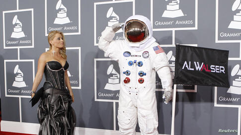 Singer Olga Levit looks on as DJ Al Walser, who is nominated for best dance recording, salutes photographers as they arrive at the 55th annual Grammy Awards in Los Angeles, California February 10, 2013.