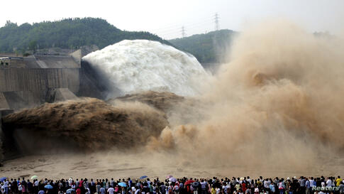 People look on as water gushes from the Xiaolangdi Reservoir section on the Yellow River, during a sand-washing operation in Jiyuan, Henan province, China, July 5, 2014.